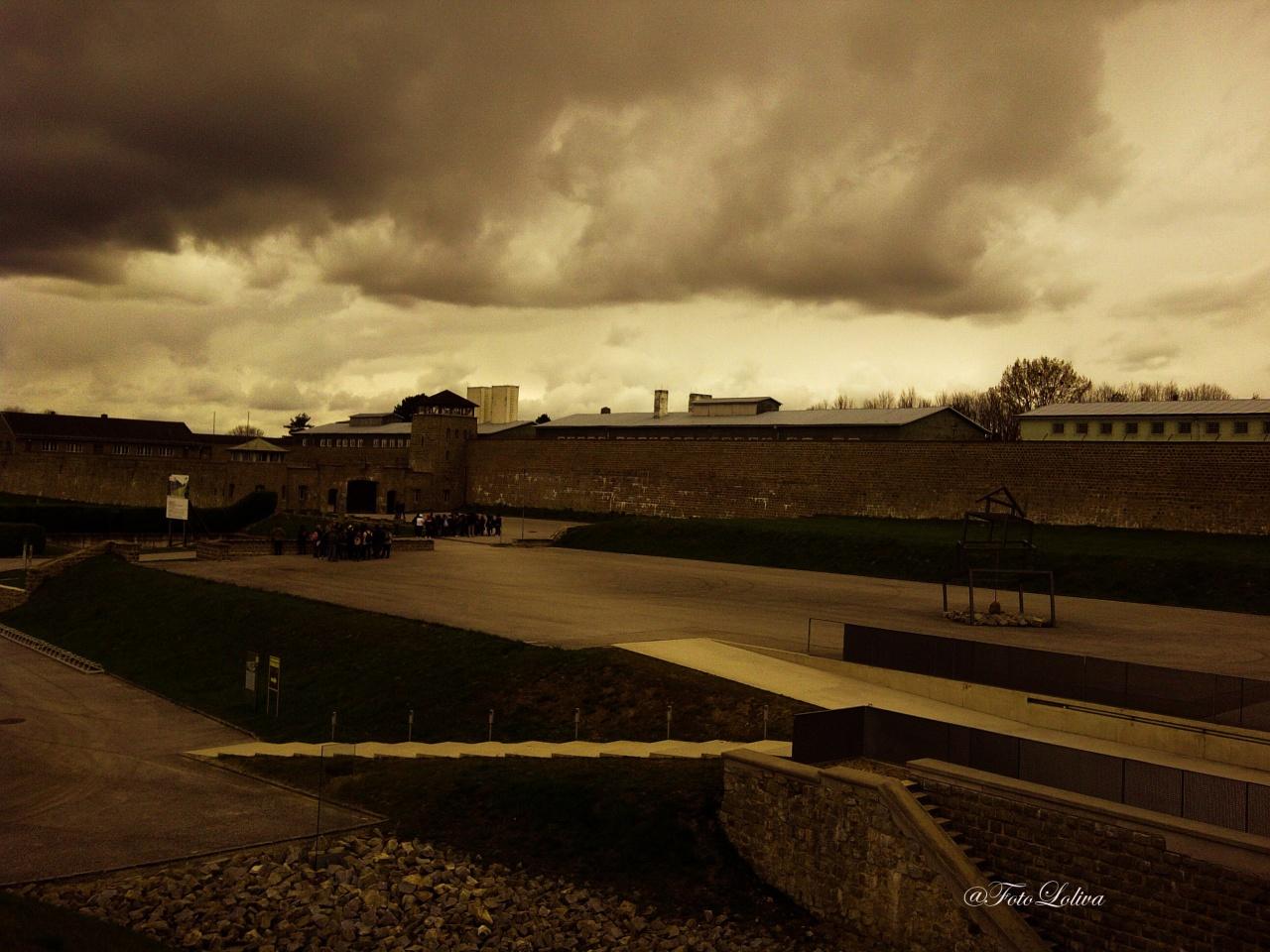 """MAUTHAUSEN - IL CAMPO - Il campo di concentramento di Mauthausen, denominato campo di concentramento di Mauthausen-Gusen dall'estate del 1940, era un lager nazista, una fortezza in pietra eretta nel 1938 in cima a una collina sovrastante la piccola cittadina di Mauthausen, nell'allora Gau Oberdonau, ora Alta Austria, situata a circa venticinque chilometri a est di Linz. Mauthausen, costruito con il granito della sottostante cava, era una estesa fortezza di pietra in uno stile vagamente orientale, tanto che l'ingresso principale al lager era chiamato dai prigionieri """"La Porta mongola"""". La fortezza, di pianta rettangolare, era chiusa su tre lati da mura di pietra spesse due metri e alte fino a otto. Il lato del lager che non si riuscì a finire fu chiuso da un reticolato di filo spinato percorso da corrente elettrica ad alta tensione, luogo di numerosi suicidi. Considerato impropriamente come semplice campo di lavoro, fu di fatto, fra tutti i campi nazisti, «il solo campo di concentramento classificato di """"classe 3"""" (come campo di punizione e di annientamento attraverso il lavoro)». Vi si attuò lo sterminio soprattutto attraverso il lavoro forzato nella vicina cava di granito e la consunzione per denutrizione e stenti, pur essendo presenti anche alcune piccole camere a gas."""