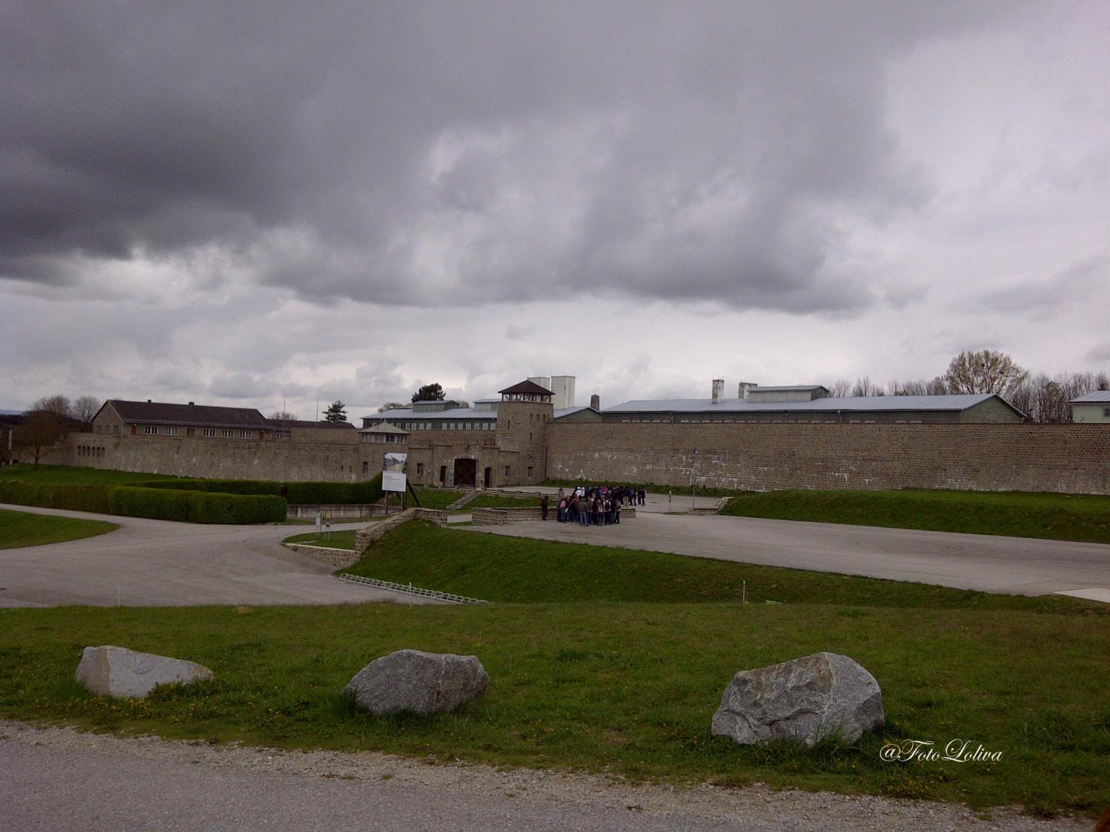 """IL CAMPO - Il comandante del lager, Franz Ziereis, accoglieva i nuovi arrivati sulla porta dell'inferno con questo agghiacciante discorso: """" Siete venuti qui per morire... qui non esiste l'uscita ma solo l'entrata; l'unica uscita è dal camino del forno crematorio..."""" E indicava i camini del crematorio. Dal tetto del Bunker, la prigione del campo di Mauthausen, fuoriuscivano tre ciminiere: una in mattoni rossi presso l'angolo esterno sinistro, per chi guarda dal piazzale dell'appello; e due di colore bianco, di diversa dimensione. Erano i camini di tre impianti di cremazione (per un totale di quattro bocche di forno), dei quali impianti oggi ne restano solo due; un terzo fu distrutto."""